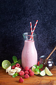 A raspberry smoothie in a glass bottle
