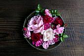 Rosa Rosenblüten im Vintage Topf auf rustikalem Holzuntergrund
