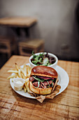 Pulled beef burger served with salad and fries