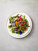 Spring salad with asparagus, buckwheat granola and edible flowers