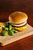 Cheese and beef burger with mustard barbecue sauce and french fries