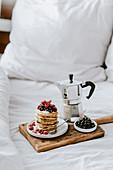 Pancakes mit Beeren und Kaffee als Frühstück im Bett
