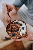 Chocolate bowl with blueberry muesli and coconut flakes