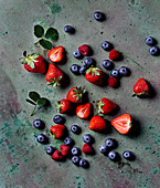 Strawberries, raspberries and blueberry on a concrete surface