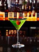 Grüner Cocktail mit Himbeere in einer Bar
