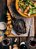 Grilled tomahawk steak on a wooden board with salad