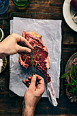 Hands marinating raw tomahawk steak with herbs