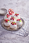 Small meringue Pavlova with whipped cream and pomegranate