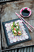 Mozzarella and courgette sushi with Parma ham on a bed of radishes
