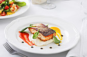 Piece of roasted red fish with basil placed on ceramic plate with various sauces on cafe table