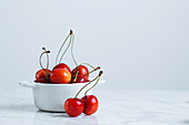 Fresh ripe red cherry with stalks in white ceramic pot