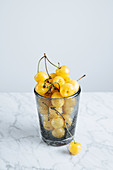 Full glass of fresh yellow cherries with stalks on marble table
