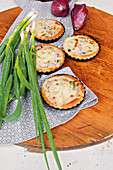Mini onion tarts with ham and mozzarella