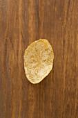 A crispy potato chip on a wooden background
