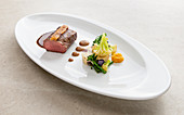 Saddle of venison in a peanut crust with ginger and orange confit