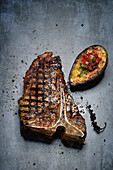 T-bone steaks with grilled avocado and tomato and coriander salsa