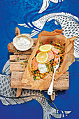 Salmon with vegetable couscous in parchment paper with mint dip