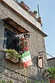 A facade with window boxes and an Italian flag