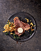 A T-bone steak with fried artichokes and marrow butter