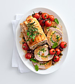 Stuffed herb roast veal with roast tomatoes and olives