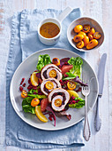 Pork roll with kumquats and cranberries on a salad with pearl barley