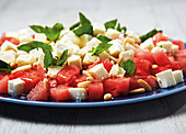 Watermelon with feta cheese, honey and pine nuts