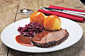 Sauerbraten (marinated pot roast) with dumplings and red cabbage