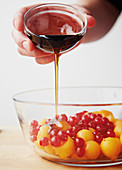 Maple syrup being poured over melon balls and redcurrants
