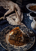 Cheese cake with delicious liquid caramel in composition with ingredients and utensil among delicate fabrics on blue marble table