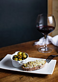 Bowl with pickled olives and bruschetta on plate placed on table with glass of red wine