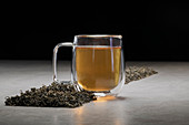 Aromatic beverage in glass mug arranged with heaps of dried tea leaves on table