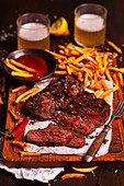 Beef steak in a sticky sauce with fries, ketchup and beer