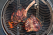 Tomahawk steak and porterhouse steak on a grill rack