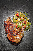 Grilled veal chop with an avocado and orange salad
