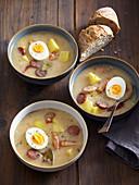 Warschauer Kartoffelsuppe mit Würstchen und gekochten Eiern