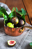 Copper pan filled with fresh figs
