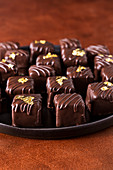 Dark chocolate homemade truffles and pralines decorated with edible gold