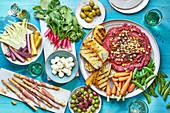 Partyplatte mit rohem Gemüse, Grissini und Rote-Bete-Hummus