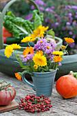 Kleiner Herbststrauß mit Ringelblumen und Astern, Kränzchen aus Hagebutten