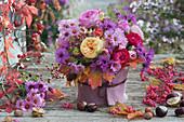 Herbststrauß aus Astern, Rosen, Fencheldolden, Hagebutten und Ahornblättern, Vase mit Filz verkleidet
