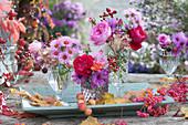 Kleine Sträuße aus Rosen, Astern, Hagebutten, Hortensie und Brombeere, Früchte vom Pfaffenhütchen, Zieräpfel und Blätter auf Holz-Schale