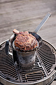 Frying steak in a pan over a grill