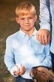 Boy holding baseball and glove