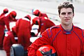 Racer holding helmet on track