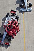 Race team surrounding racer on track