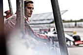 Racer standing on sidelines on track