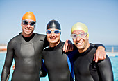 Triathletes in wetsuits smiling together