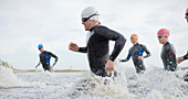Triathletes in wetsuits running in waves
