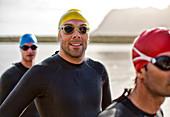 Triathletes in wetsuit smiling in water