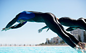 Triathletes diving into swimming pool